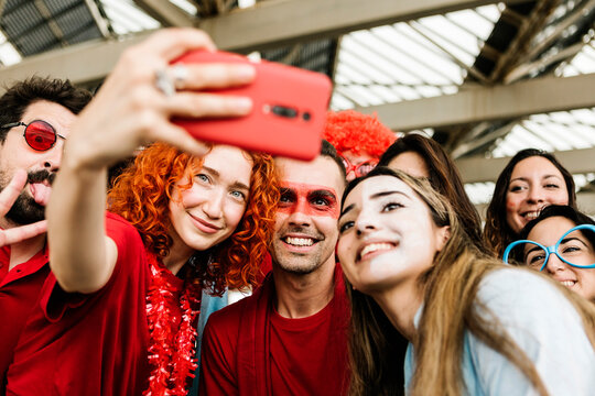 Multiethnic group of young people taking selfie out of the stadium - Football fans having fun together - Focus on painted face man