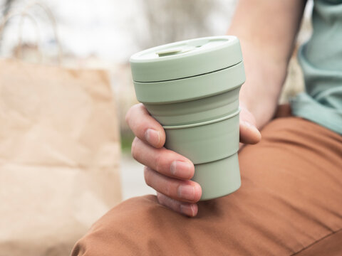 Collapsible silicon eco cup for takeaway coffee. Male hand with sustainable mug.