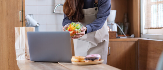 A female video blogger cooking food in the kitchen and filming for online learning cooking class concept