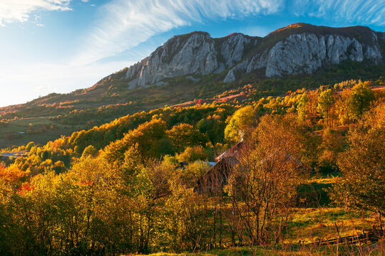 rocky formation in apuseni mountains at sunset. gorgeous autumn landscape in evening light. trees on the hills in colorful foliage. location masivul-vulcan, hunedoara country of romania