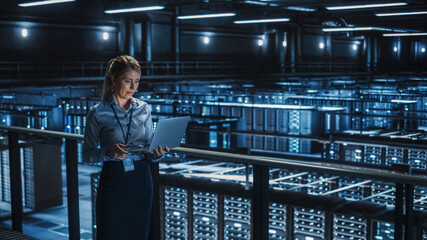 Data Center Female It Specialist Using Laptop. Server Farm Cloud Computing and Cyber Security Maintenance Administrator Working on Computer. Information Technology Professional.