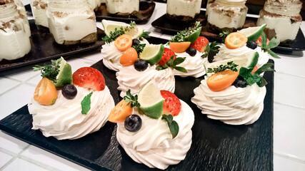 Anna Pavlova desserts on a black plate and jars of tirramissu on background