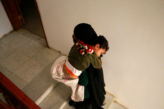 Mother of Muhammad Abu Baker carries him at al-Shafaqa charity where he receives medical support during his treatment for cancer in Sanaa