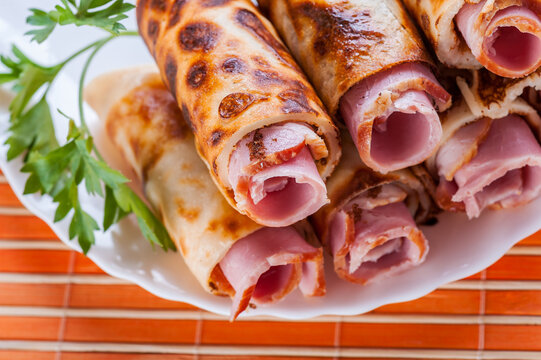 Delicious bacon is wrapped in pancakes with a tube, next to a green parsley. Food in a white plate on an orange bamboo mat.