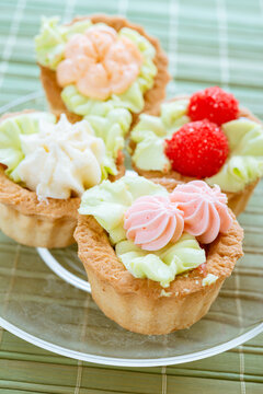 Delicious sweet sandbag baskets with cream on a green bamboo tablecloth.