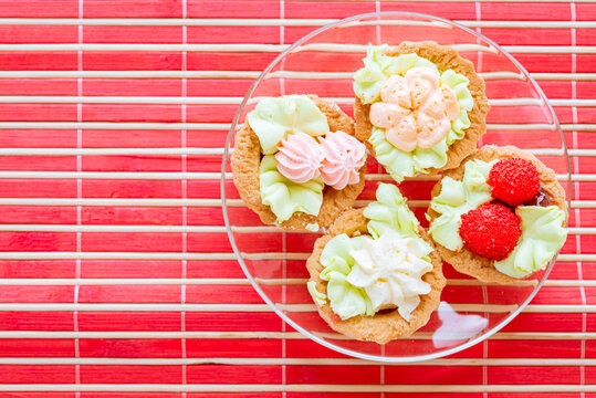 Delicious sweet sandbreaking baskets with cream in a glass plate on a red bamboo mat.