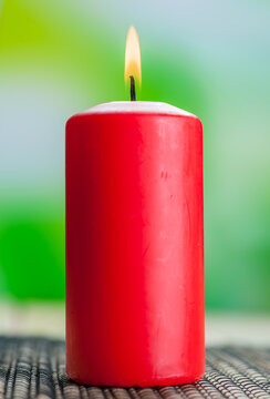 Burning red candle stands on the bamboo tablecloth on the table.