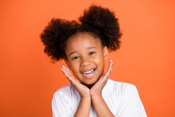 Photo of small cute girl hands face wear white t-shirt isolated on orange color background