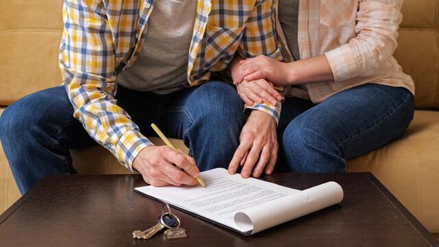 Husband signs apartment purchase contract on table near keys with house shaped breloque sitting with wife on sofa in room close view
