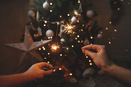Hands holding burning sparklers on background of christmas tree and glowing star in festive scandinavian room. Happy New Year! Couple celebrating with firework bengal lights. Atmospheric moment