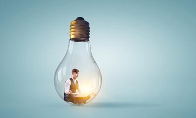 Businessman doing yoga in lotus pose inside light bulb
