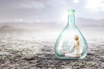 Business woman doing yoga in lotus pose inside glass bottle
