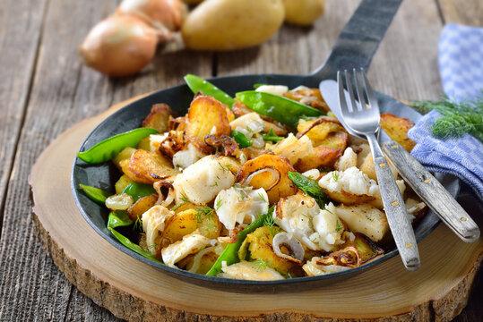 Deftiges Fischgröstl mit Bratkartoffeln, Heilbutt und Zuckerschoten - Fried potatoes with pieces of halibut fillet, sugar peas and onion rings, often served in a frying pan