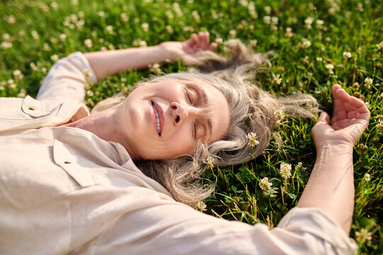 Woman with drooping eyelids lying on grass