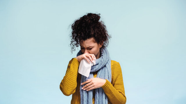 sick woman in warm sweater wiping nose with paper napkin isolated on blue