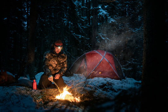 Man at log fire in winter forest