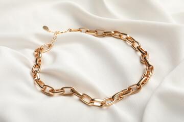 Elegant golden necklace on white fabric. Stylish bijouterie
