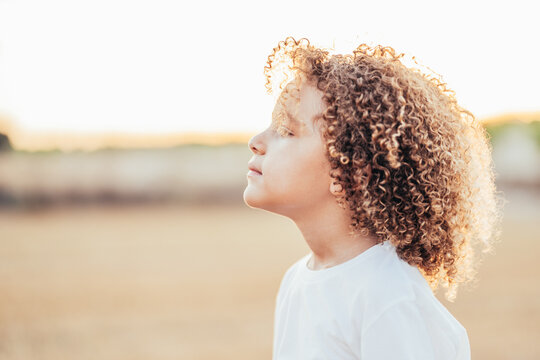 Carefree curly haired ethnic child in field