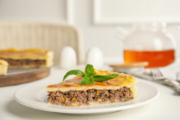 Piece of delicious pie with minced meat on white table indoors