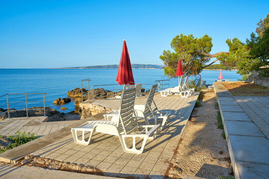 Parasols and sun loungers at a typical bathing place on the coast of the town of Krk on the Adriatic Sea in Croatia