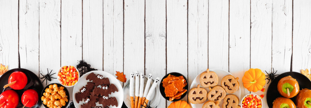 Traditional Halloween treat bottom border over a white wood banner background with copy space. Top view. Variety of candied apples, cookies, candy and sweets.