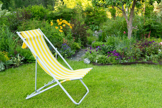 Beautiful flower garden with green lawn and yellow garden chair on it in summer