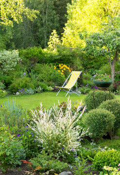 Beautiful flower garden with green lawn and yellow garden chair on it in summer, vertical (sharpness at the leading edge of the frame)
