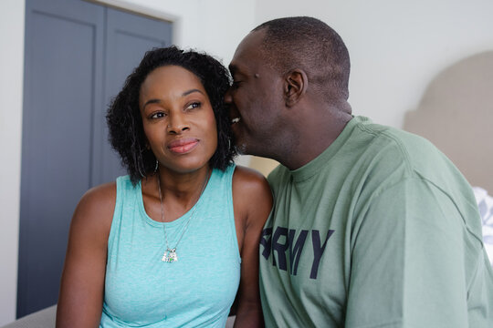 Black man husband whispering to wife