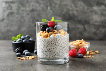 Delicious chia pudding with berries, granola and mint on grey table