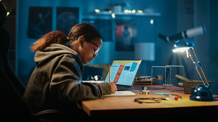 Young Teenage Multiethnic Schoolgirl is Studying Science Topic About Robotics at Home. Girl is Working on Homework for School. Young Female Reading Research Articles About Her Hobby. Education Concept
