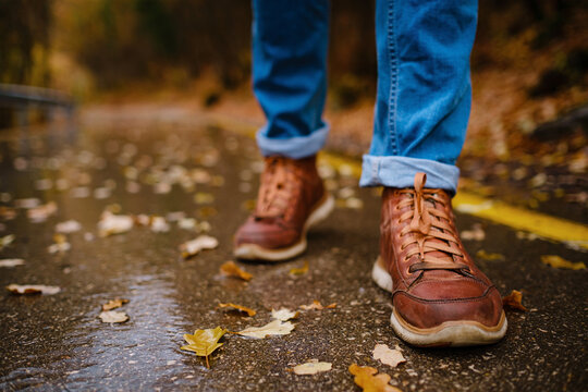feet of a woman walking along asphalt road in autumn forest in the rain. Pair of shoe on slippery road in the fall. Abstract empty blank of the autumn weather