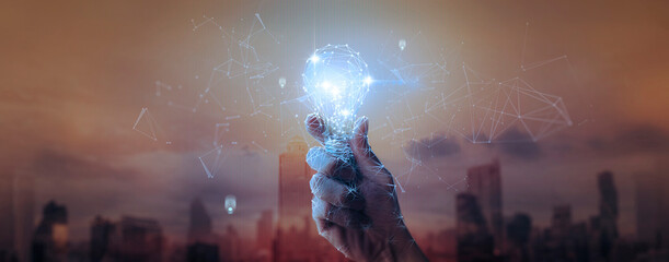 Hand businessman holding light bulb with mesh light line.future technology,Alternative energy,idea,saving electricity innovation and inspiration concepts.