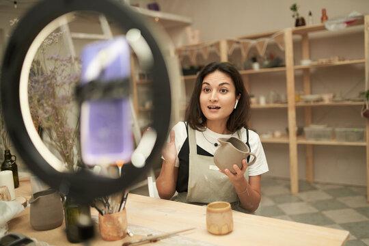 Female potter recording video for vlog