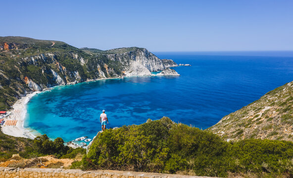 Panoramic aerial photo of man standing on top of a rock with an exciting feeling of freedom, looking at Petani Beach. Kefalonia ionian island, Greece