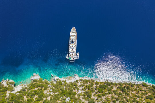 Aerial top down view of luxury lonely yacht boat in turquoise blue sea on secluded remote coast of Kefalonia Ionian island, Greece