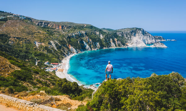 Man standing on top of a rock with an exciting feeling of freedom, looking at Petani Beach. Kefalonia ionian island, Greece