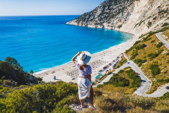 Happy woman standing on top of a rock with hat enjoying Myrtos Beach. Cephalonia island, Greece
