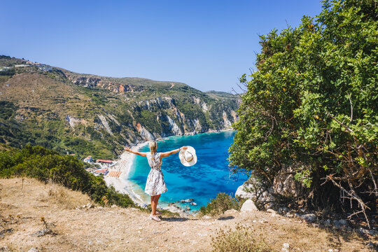Happy woman raising hands with an exciting feeling of freedom, looking at Petani Beach. Cephalonia island, Greece