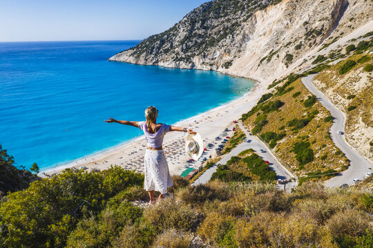 Happy woman standing on top of a rock, raising hands with an exciting feeling of freedom, looking at Myrtos Beach. Cephalonia island, Greece