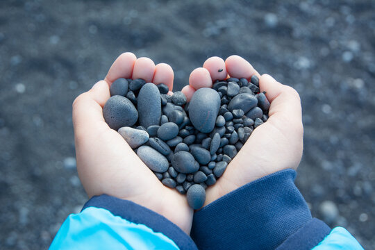 Hands holding small black stones, heart shaped