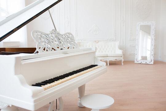 White grand piano standing in elegant classical interior