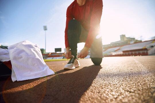 Man runner in sportswear prepare for training on stadium