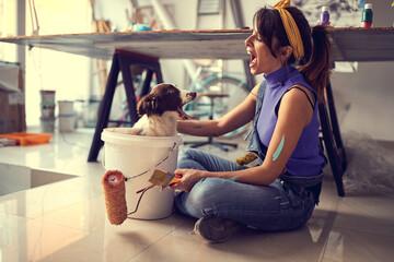 Caucasian female artist having fun with her dog