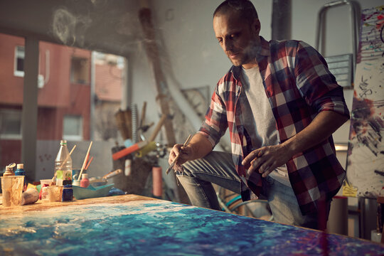 Focused male painter artist creating a new piece