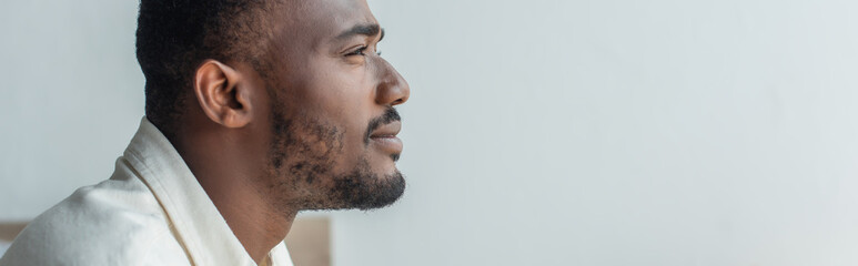 side view of pensive young african american man looking away, banner