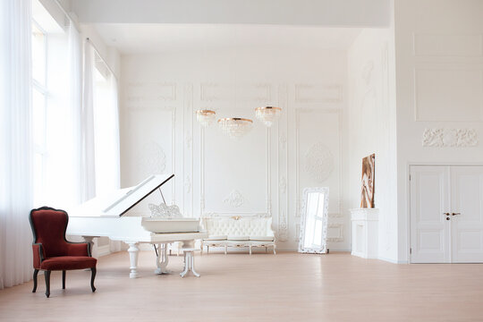 Rich luxury interior of a classic style room with vintage furniture, big windows, mirror, chandeliers and grand piano.