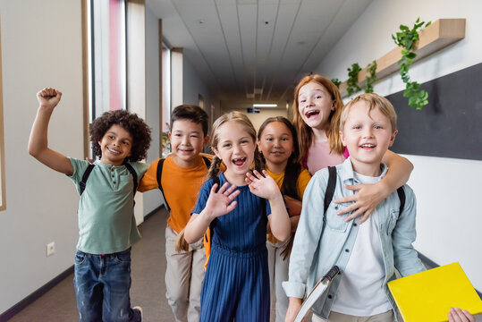 cheerful multiethnic kids embracing, waving hands and showing rejoice gesture at school