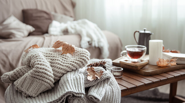 Autumn home composition with tea, candle, book and knitted elements.