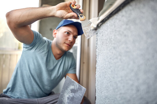 Man working on a house facade.