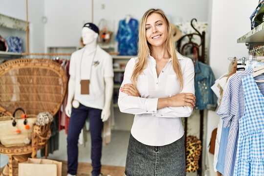 Young caucasian customer woman smiling happy standing with arms crossed gesture at clothing store.